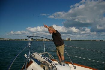 Arm signals are a great form of communication- no shouting over the wind required. On this Kadey Krogen the mate is pointing to where the anchor is and directing the helmsman where to drive.